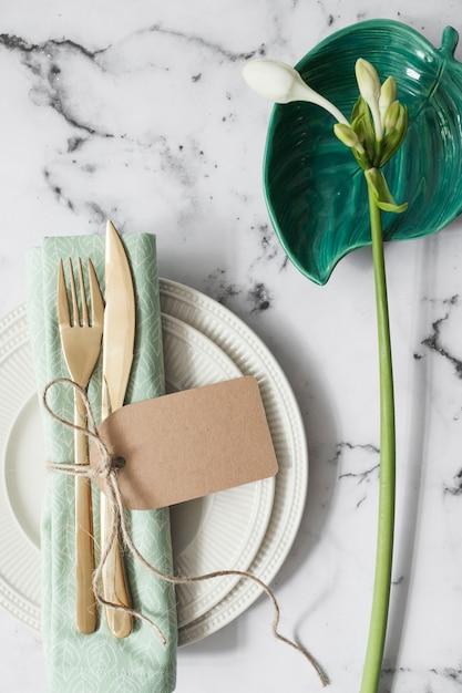 Couverteer met witte borden; gevouwen servet en bestek met witte bloemen Gratis Foto