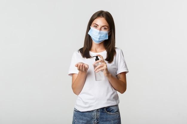 Covid-19, gezondheids- en sociaal afstandsconcept. aantrekkelijke jonge donkerbruine vrouw die in medisch masker wit handdesinfecterend middel toepast. Gratis Foto