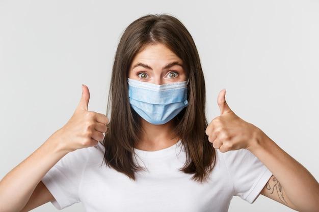 Covid-19, gezondheids- en sociaal afstandsconcept. close-up van blij aantrekkelijk meisje in medisch masker met thumbs-up in goedkeuring. Gratis Foto