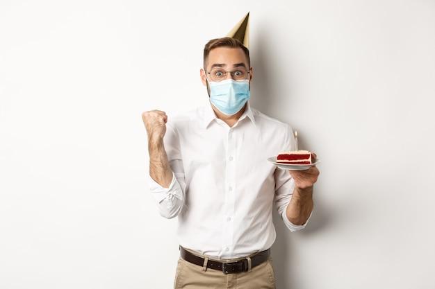 Covid-19, sociale afstand nemen en vieren. hoopvolle gelukkige verjaardag man in gezichtsmasker, verjaardagstaart vasthouden en zich verheugen, staan Gratis Foto