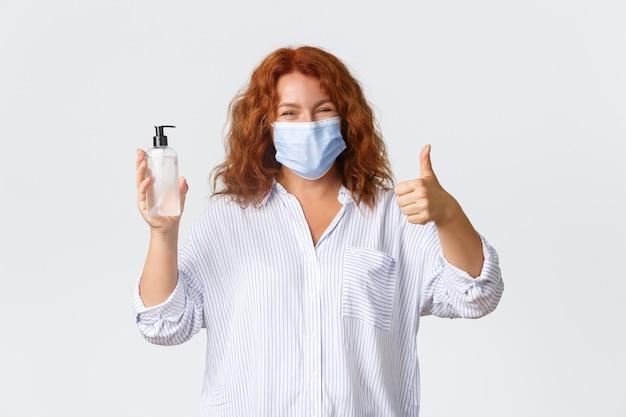 Covid-19 sociale afstand nemen, maatregelen ter voorkoming van coronavirus en mensenconcept. glimlachende, schattige roodharige dame van middelbare leeftijd raadt handdesinfecterend middel aan, toont duimen omhoog en draagt een medisch masker. Gratis Foto