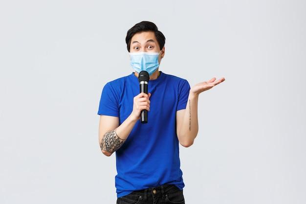 Covid019 levensstijl, mensenemoties en vrije tijd op quarantaineconcept. enthousiaste aziatische man in medische masker hebben spraak, met behulp van microfoon, stand-up comedy acteur grappen te vertellen aan het publiek Premium Foto