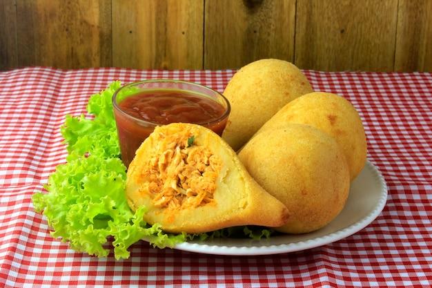 Coxinha in het gerecht, traditionele braziliaanse gerechten snacks gevuld met kip Premium Foto