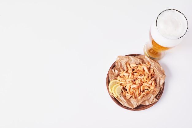 Crackers en chips met een glas bier op wit. Gratis Foto