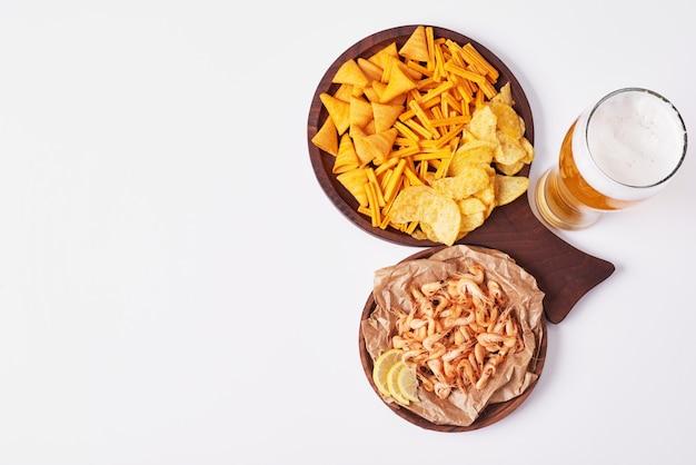 Crackers en chips met een glas bier. Gratis Foto