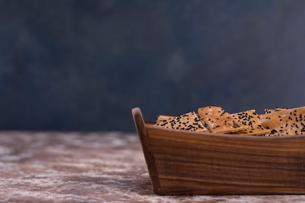 Crackers met zwarte komijn erop in houten bakje. Gratis Foto