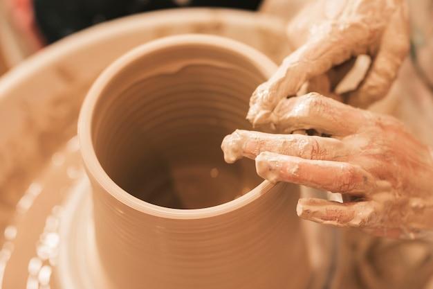 Craftswoman vormt de aarden pot met zijn handen op een aardewerkwiel Gratis Foto