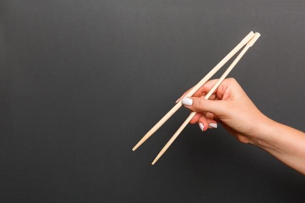 Creatief beeld van houten eetstokjes in vrouwelijke hand op zwarte. japans en chinees eten met copyspace Premium Foto