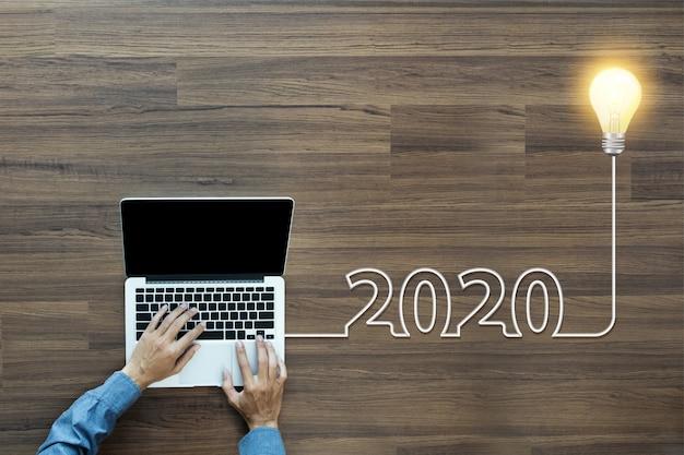 Creatief gloeilampenidee 2020 nieuw jaar, met zakenman die aan laptop werken Premium Foto