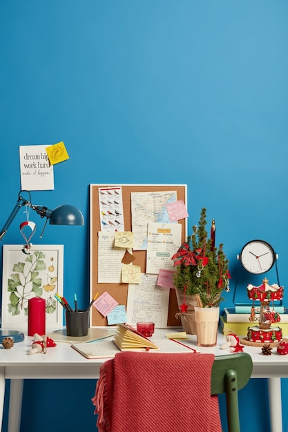 Creatief ingerichte werkplek van student of wetenschapper, gesloten notitieblok op tafel, bureau met geplakte handgeschreven notities Gratis Foto