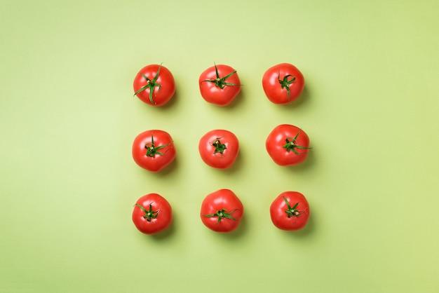 Creatief patroon van rode tomaten. minimaal ontwerp. vegetarisch, veganistisch, biologisch voedsel en alkalisch maaltijdconcept Premium Foto