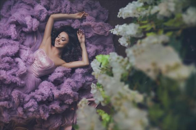 Creatief portret van een mode-vrouw in prachtige lange roze romantische jurk op de vloer liggen. bovenaanzicht Premium Foto