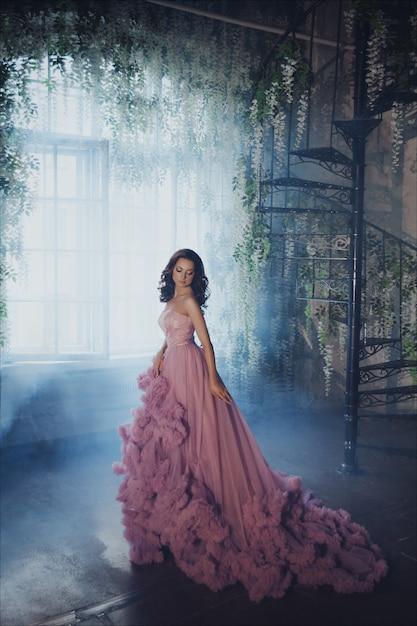 Creatief portret van een mode-vrouw in prachtige lange roze romantische jurk Premium Foto