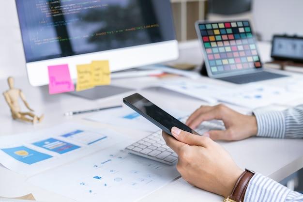 Creatief startup front-end ontwerpers team dat zich concentreert op computerscherm voor het ontwerpen, coderen, programmeren van mobiele applicaties. Premium Foto