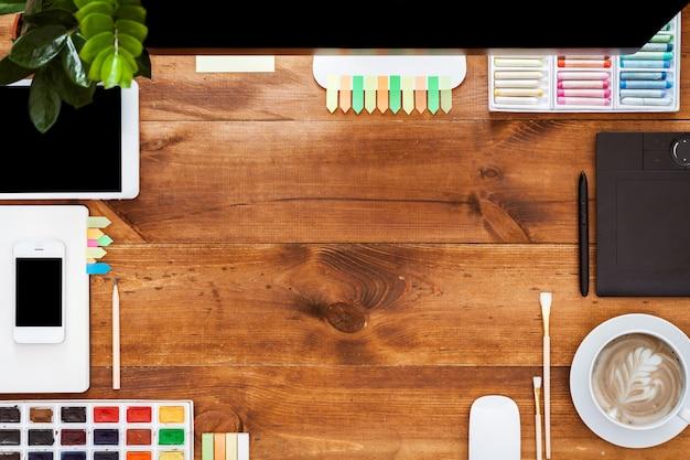 Creatief werktafel ontwerpconcept, computer verf op bruin houten bureau Premium Foto