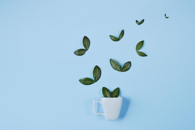 Creatieve compositie. koffiekopje met vogels gemaakt van natuurlijke groene bladeren op blauwe achtergrond Premium Foto