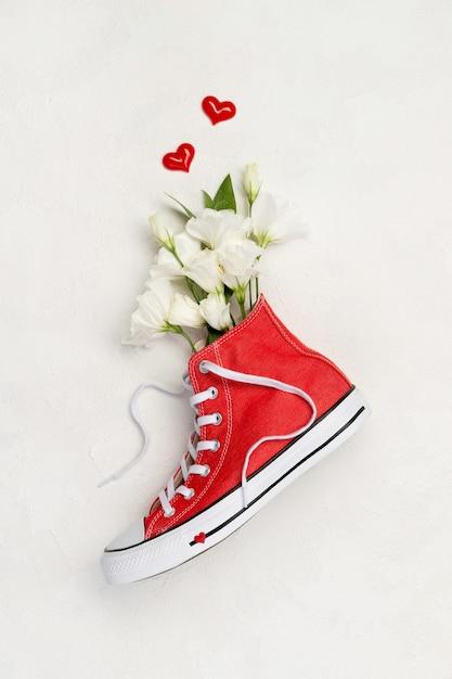 Creatieve compositie met rode sneakers en bloemen op witte achtergrond. verjaardag dames dag moeders dag wenskaart. Premium Foto