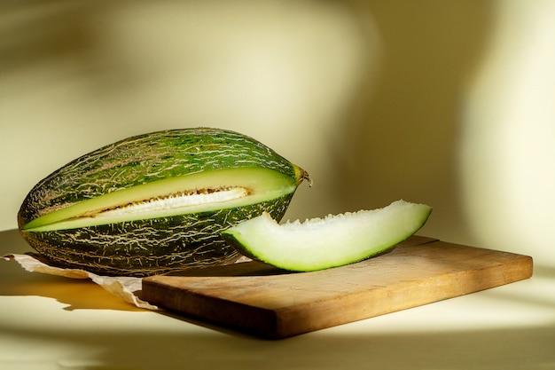 Creatieve foto van smakelijke meloen en segment van watermeloen op gele achtergrond met schaduwen. sluit omhoog mening over de zoete meloen van het de zomerfruit. eten foto concept. kunstwerk met watermeloen Premium Foto