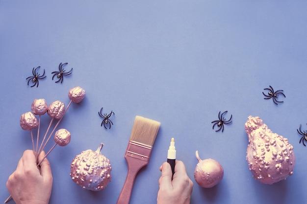 Creatieve halloween plat lag op grijs papier op lichtpaarse muur met kopie-ruimte. vrouwelijke handen met marker en kleine geschilderde pompoenen, plastic spinnen en kwast. Premium Foto