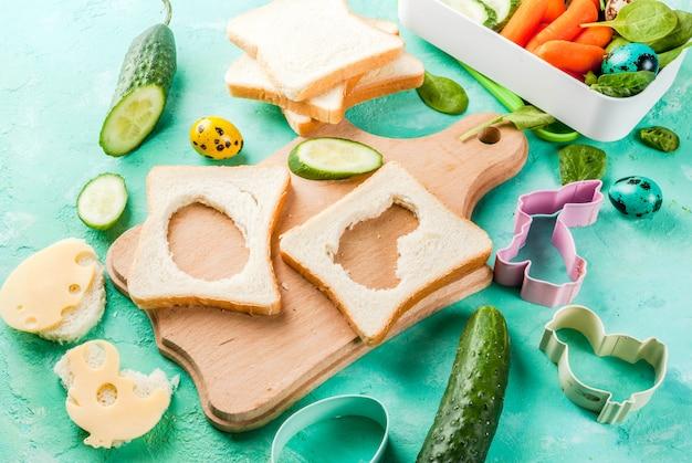 Creatieve kinderontbijt lunchbox voor pasen, sandwiches met kaas, verse groenten - komkommers, wortels, spinazie, kleurrijke kwarteleitjes. lichtblauwe tafel, kopieer ruimte Premium Foto