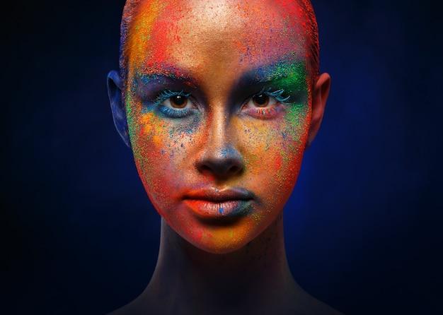 Creatieve kunst make-up. portret van jonge mode-model met heldere kleurrijke mix van verf op haar gezicht. kleurfantasie, artistieke make-up. Premium Foto