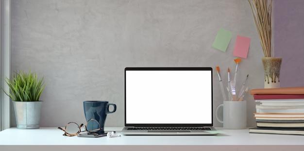 Creatieve kunstenaarsstudio met leeg scherm laptop en tekengereedschappen Premium Foto