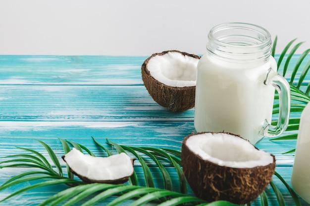 Creatieve lay-out gemaakt van kokosnoten en tropische bladeren. voedsel concept Premium Foto
