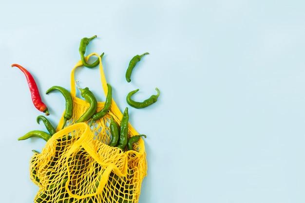 Creatieve lay-out groene chili pepers. groene groenten in gele string zak op pastel blauwe achtergrond. hoop groene peper genaamd frigitelli Premium Foto