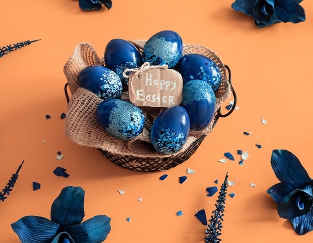 Creatieve pasen-indeling gemaakt van kleurrijke eieren en bloemen op blauwe achtergrond. cirkel krans plat lag concept. het concept van de paasvakantie. Gratis Foto
