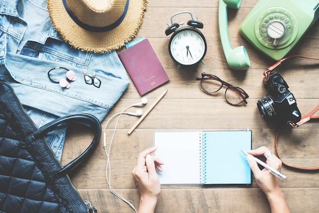 Creatieve platte lay-out van vrouwen handen planning vakantie vakantie met accessoires op houten werkruimte Premium Foto