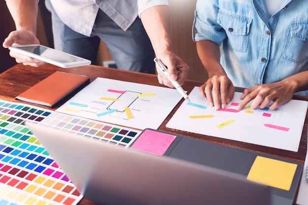 Creatieve ui-ontwerper teamwerk vergadering planning ontwerpen draadframe lay-out applicatie-ontwikkeling op smartphonescherm voor web mobiele telefoontechnologie. Premium Foto