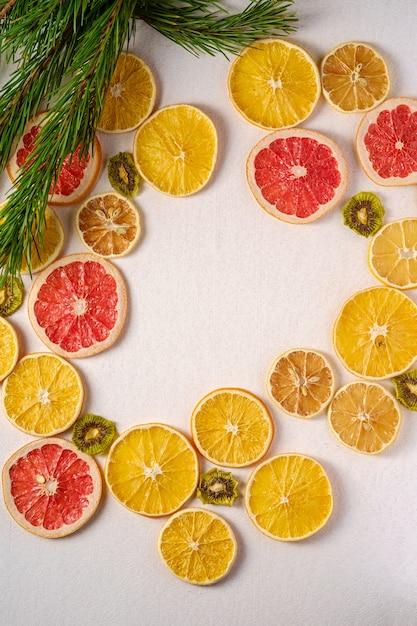 Creatieve vakantie kerstmis nieuwjaar voedsel fruit textuur met gedroogde grapefruit, kiwi, sinaasappel en citroen met tak van dennenboom Premium Foto