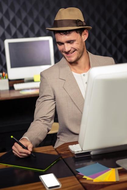 Creatieve zakenman die computer en grafische tablet gebruikt Premium Foto