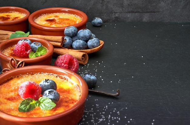 Creme brulee met bessen en ingrediënten op donkere steen, ruimte Premium Foto