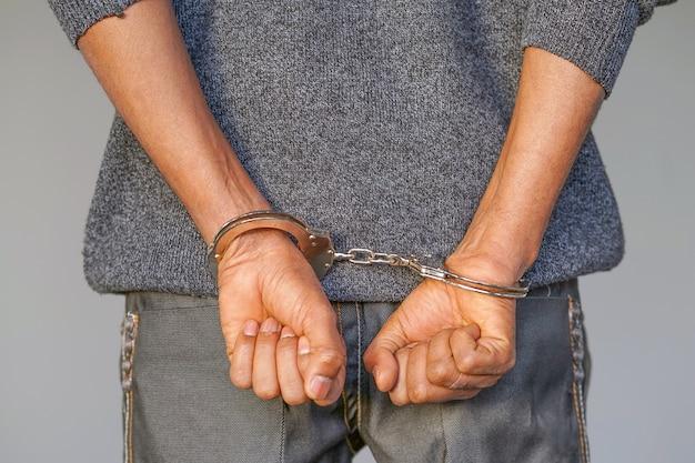 Criminele handen opgesloten in handboeien. vergrote weergave Premium Foto