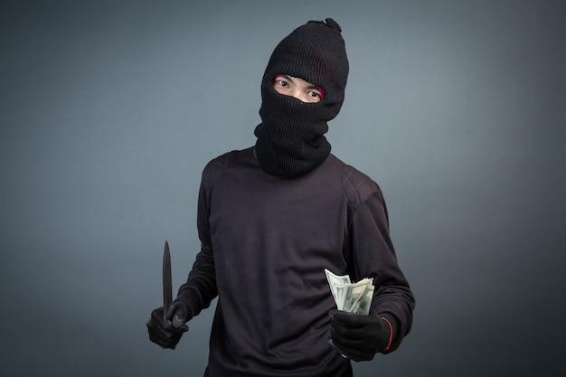 Criminelen dragen een zwart masker en houden donker op grijs Gratis Foto