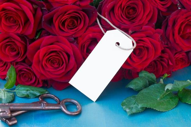 Crimson rozen op blauwe tafel met lege tag Premium Foto