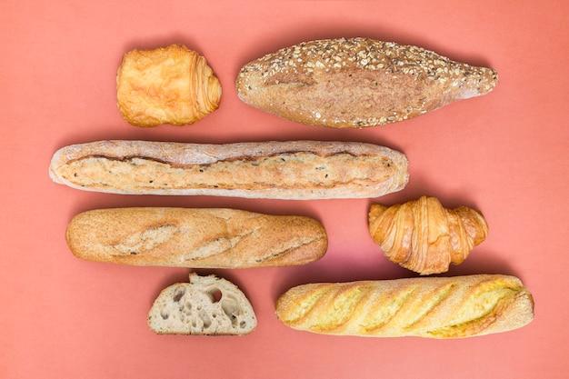 Croissant; bladerdeeg; brood en baguette broden op gekleurde achtergrond Gratis Foto