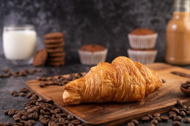 Croissant geplaatst op een houten platform met koffiebonen op een zwarte cementvloer. Gratis Foto