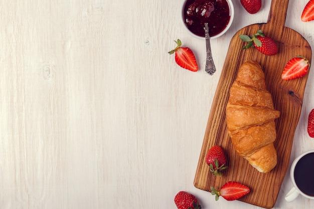 Croissant met aardbeienjam op een houten bord Premium Foto