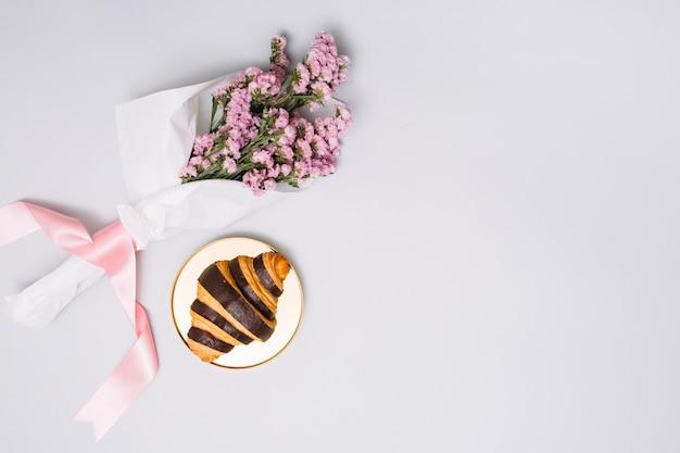 Croissant met bloemenboeket op lijst Gratis Foto