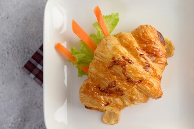 Croissant met hotdog op witte schotel Gratis Foto