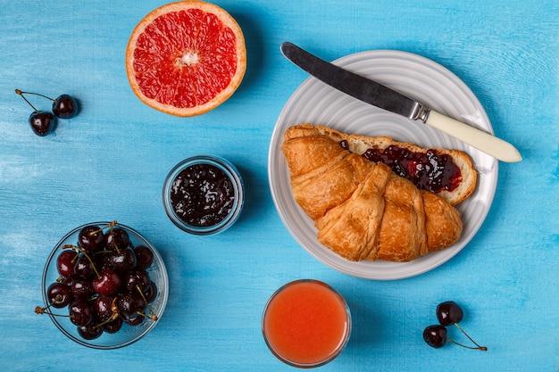 Croissant met kersenjam en grapefruitsap Premium Foto