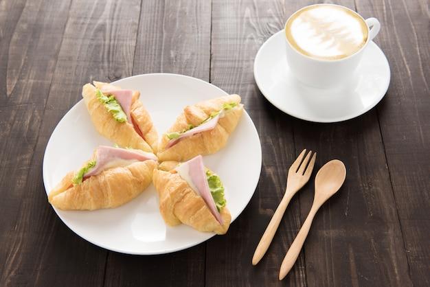 Croissant met parmaham en koffie op houten tafel Premium Foto