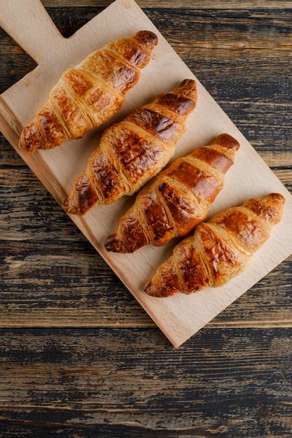 Croissant plat lag op houten en snijplank Gratis Foto