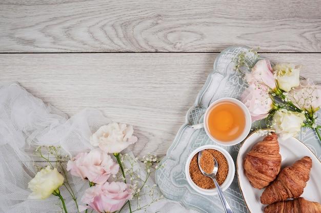 Croissants en bloemen in plat leggen Gratis Foto