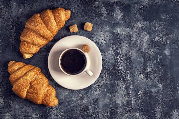 Croissants en een witte kop koffie Premium Foto