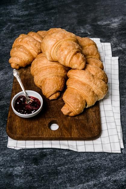Croissants en pot met jam opzij op grijze tafel Gratis Foto