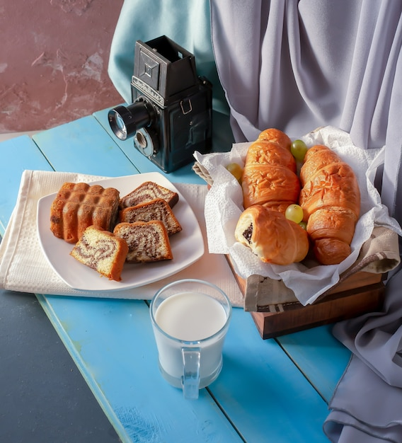 Croissants en vanille taart op de tafel met een glas melk. Gratis Foto