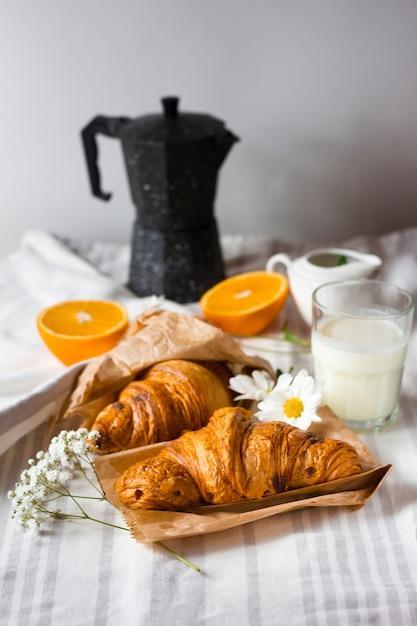 Croissants met gesneden sinaasappels en melk Gratis Foto